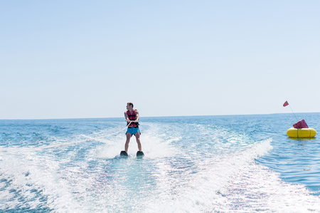 Young man glides on water skiing on the waves on the sea, ocean. Healthy lifestyle. Positive human emotions, feelings, joy.