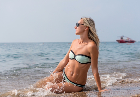 Happy smiling young woman in black sunglasses in the sea in the day time. Positive human emotions, feelings, joy. Spring and summer holidays. Banque d'images - 95963534