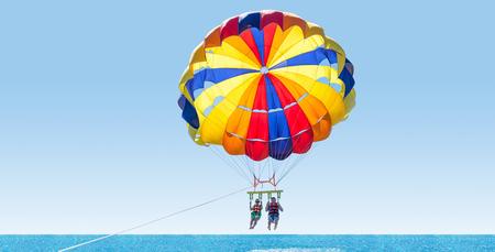 Gelukkig paar Parasailing op Tropisch Strand in de zomer. Paar onder parachute opknoping medio lucht. Plezier hebben. Tropisch paradijs. Positieve menselijke emoties, gevoelens, familie, reizen, vakantie.