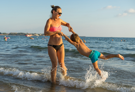 Young mother and smiling baby boy son playing on the beach in the day time. Positive human emotions, feelings, joy. Funny cute child making vacations and enjoying summer. Spring and summer holidays.