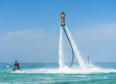 Father and his daughter posing at new flyboard at Caribbean tropical beach. Positive human emotions, feelings, joy. Funny cute child making vacations and enjoying summer.