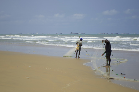 Fishermen catch fish with nets near africa cost . Big cargo ships and oil tankers in Lagos, Nigeria, Africa.