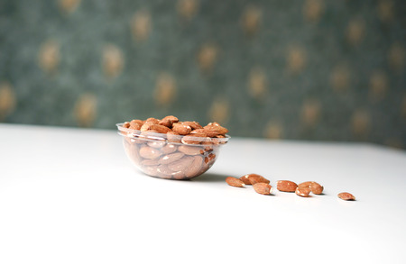 Healthy food  for background image close up almond nuts. Texture on white grey table top view. Nuts on the cup plate