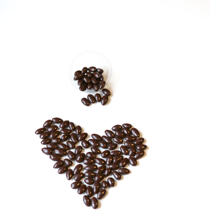 Nuts arranged in heart shape on background. Food image close up candy, chocolate milk, extra dark almond nuts. Love Texture on white grey table top view