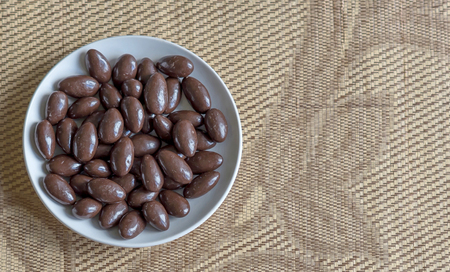 Food image close up candy, chocolate milk, extra dark almond nuts. Texture on view background on the cup plate 写真素材