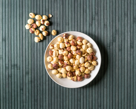 Healthy food  for background image close up hazelnuts.  Nuts texture on top view on the cup plate Фото со стока