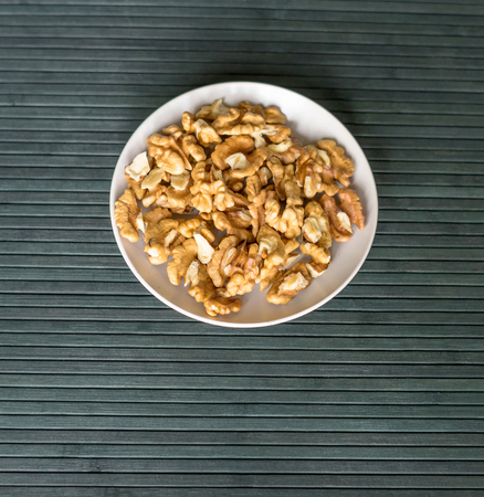 Healthy food for background image close up walnuts. Nuts texture on top view on the cup plate