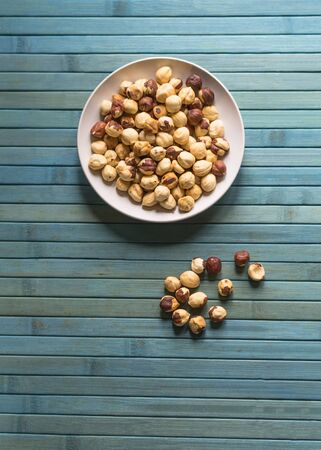 Healthy food  for background image close up hazelnuts.  Nuts texture on top view on the cup plate Banco de Imagens