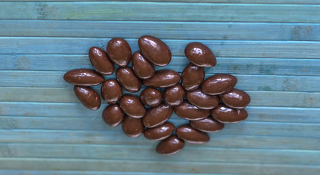 Food image close up candy, chocolate milk, extra dark almond nuts. Texture on top view background