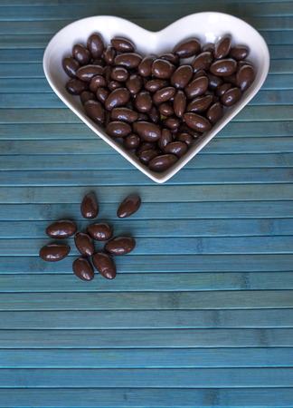 Nuts arranged in heart shape on background. Food image close up candy, chocolate milk, extra dark almond nuts. Love Texture 写真素材