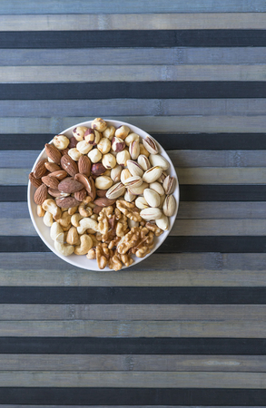 Healthy food. Nuts mix assortment on stone texture top view. Collection of different legumes for background image close up nuts, pistachios, almond, cashew nuts, peanut, walnut. image Фото со стока