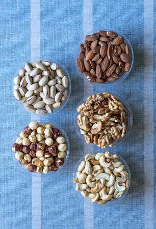 Healthy food. Nuts mix assortment on stone texture top view. Collection of different legumes for background image close up nuts, pistachios, almond, cashew nuts, peanut, walnut. image Banco de Imagens