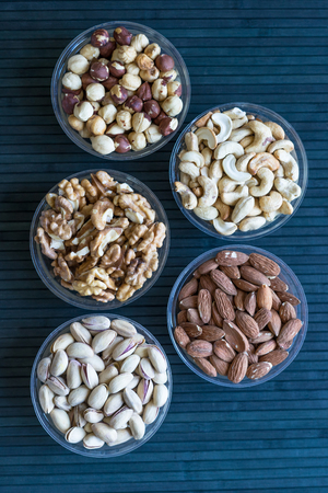 Healthy food. Nuts mix assortment on stone texture top view. Collection of different legumes for background image close up nuts, pistachios, almond, cashew nuts, peanut, walnut. image Imagens