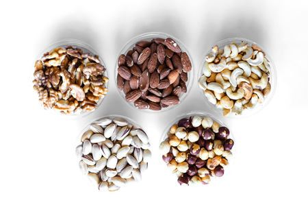 Healthy food. Nuts mix assortment on white grey table top view. Collection of different legumes for background image close up nuts, pistachios, almond, cashew nuts, peanut, walnut. image Фото со стока