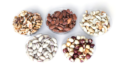 Healthy food. Nuts mix assortment on white grey table top view. Collection of different legumes for background image close up nuts, pistachios, almond, cashew nuts, peanut, walnut. image Stock Photo