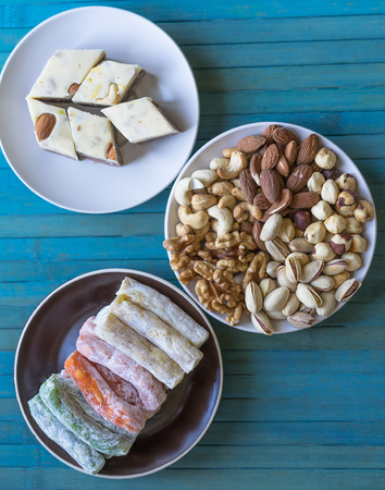 Traditional Turkish Delight. Oriental dessert halva on a  plate. Isolated on background. Eastern delicacy sweets. Healthy food. Nuts mix assortment. Collection of different legumes for image close up nuts, pistachios, almond, cashew nuts, peanut, walnut on top view