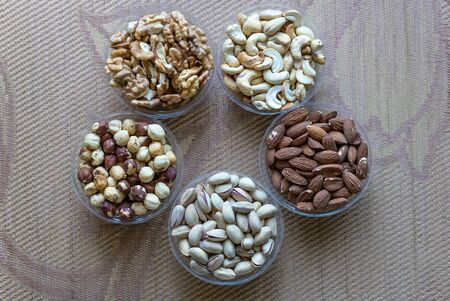 Healthy food. Nuts mix assortment on stone texture top view. Collection of different legumes for background image close up nuts, pistachios, almond, cashew nuts, peanut, walnut. image Imagens - 124852530