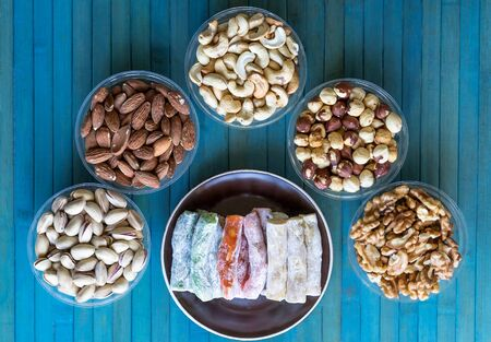 Traditional Turkish Delight. Oriental dessert on a  plate. Isolated on background. Eastern delicacy sweets. Healthy food. Nuts mix assortment. Collection of different legumes for image close up nuts, pistachios, almond, cashew nuts, peanut, walnut on top view Imagens