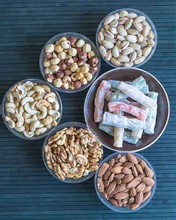 Traditional Turkish Delight. Oriental dessert on a  plate. Isolated on background. Eastern delicacy sweets. Healthy food. Nuts mix assortment. Collection of different legumes for image close up nuts, pistachios, almond, cashew nuts, peanut, walnut on top view.