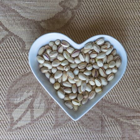 Nuts arranged in heart  on background. Healthy Food image close up pistachios on the cup plate. Love Texture on top view mock up Imagens