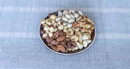 Healthy food. Nuts mix assortment on stone texture top view. Collection of different legumes for background image close up nuts, pistachios, almond, cashew nuts, peanut, walnut. image Imagens - 124853707