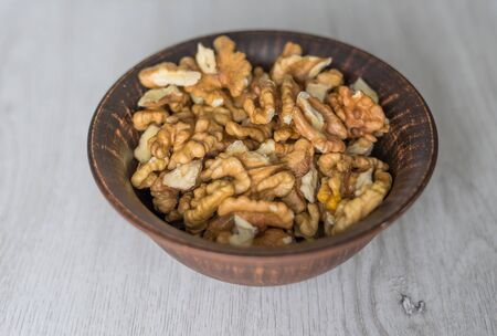 Healthy food  for background image close up walnuts.  Nuts  texture on white grey table top view on the cup plate