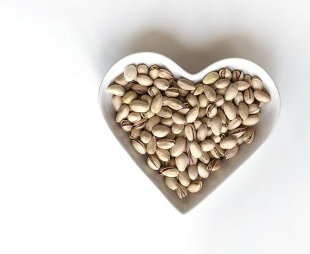 Nuts arranged in heart  on background. Healthy Food image close up pistachios on the cup plate. Love Texture on white grey table top view mock up