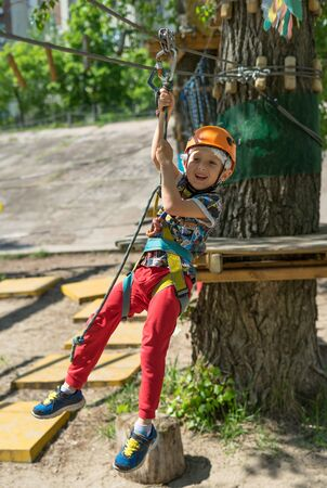 Boy at climbing activity in high wire forest park. Table Mountain Cableway kids special on again.