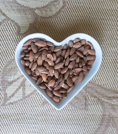 Nuts arranged in heart  on background. Healthy Food image close up almond on the cup plate. Love Texture on top view mock up