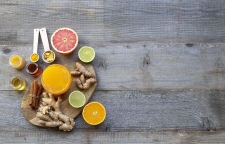 Top view on the immune system booster - orange juice, ginger, turmeric, citruses, and honey on the old wooden table