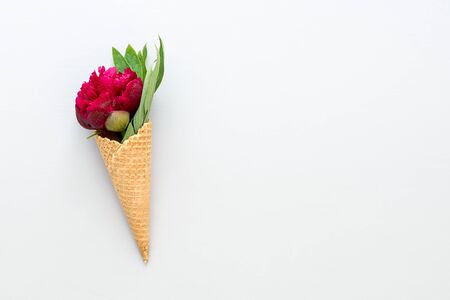 Waffle cone with beautiful red peony flower and leaves on grey concrete background. Top view, copy space.