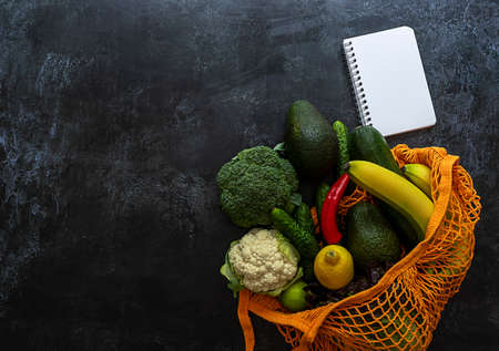 The concept of grocery shopping. String bag with vegetables, fruits, and white notebook. Copy space for text, top view.