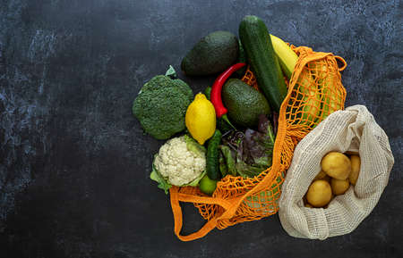 Concept of grocery shopping. String bag with vegetables, fruits, and potatoes. Copy space for text, top view.