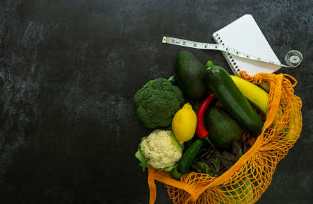 Healthy grocery shopping for loose weight. String bag with vegetables, fruits, empty white notebook, and inch measuring tape. Copy space for text, top view.