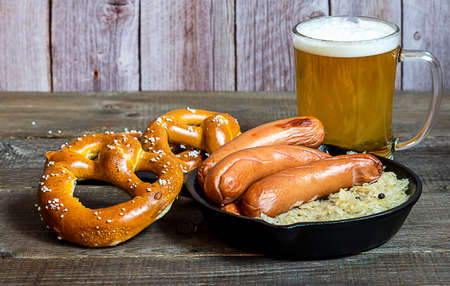 Oktoberfest traditional food. German sausages bratwurst with sauerkraut, beer, and pretzels on the wooden table.