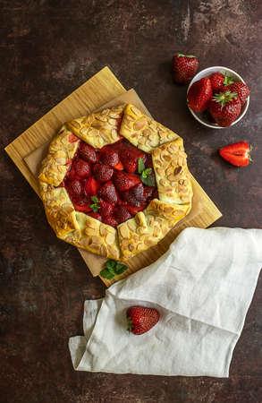 Vertical flat lay of homemade strawberry open pie galette. Sommer baking, ripe berries 版權商用圖片