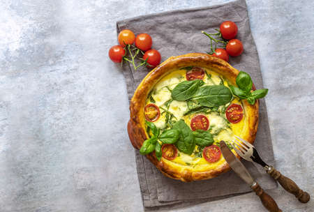 Vegetarian open pie or french quiche with spinach, feta, and mozzarella cheese, and tomatoes cherry. top view, copy space.