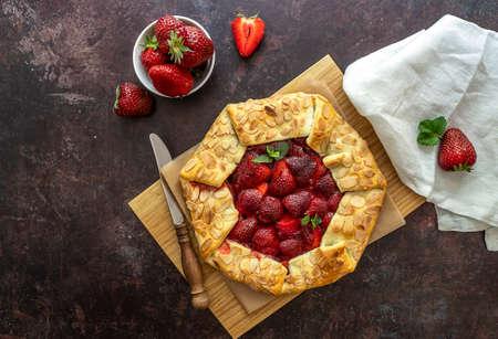 Freshly baked strawberry open pie galette on the cutting board. 版權商用圖片