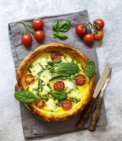 Vegetarian quiche with spinach, feta, and mozzarella cheese, and tomatoes cherry. Top view, rustic cutlery 版權商用圖片