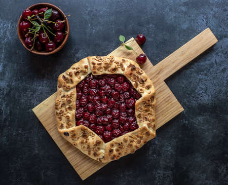 View over the above of homemade cherry open pie galette with hazelnut petals on the wooden board.