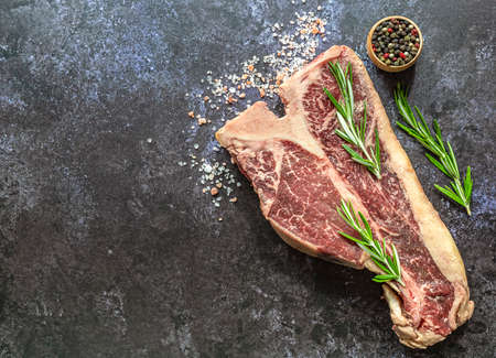 Preparing raw thick T-bone Steak for grill or BBQ. Top view, copy space for text.