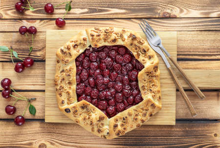Flat lay of homemade cherry open pie galette with hazelnut petals. Sommer baking.