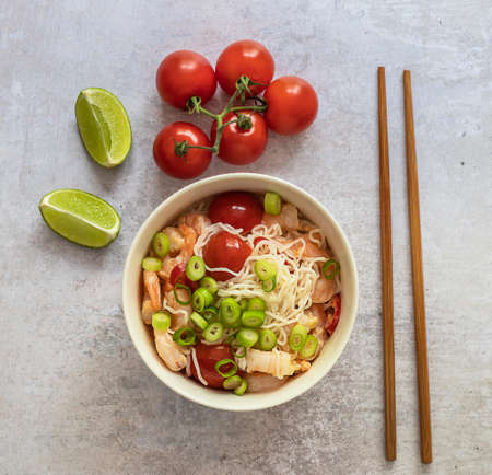 Close up of keto lunch in asian style. Shirataki noodles with shrimps, tomatoes cherry, coconut milk, and chili. Low carb gluten-free ketogenic diet meal.