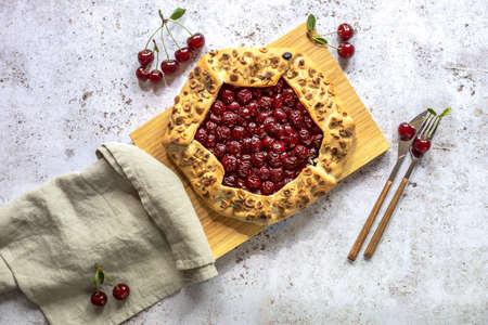 Sour cherry open pie or galette. Summer baking concept.