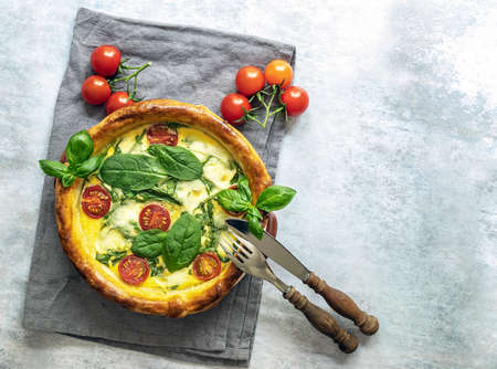 French quiche with spinach, feta, and mozzarella cheese, and tomatoes cherry. top view, copy space. 版權商用圖片