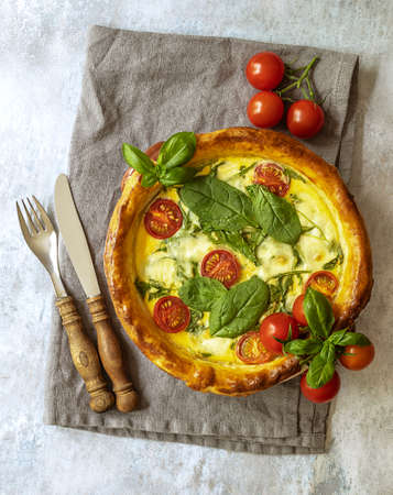 French vegetarian quiche with spinach, feta, and mozzarella cheese, and tomatoes cherry. Vertical orientation, rustic cutlery 版權商用圖片