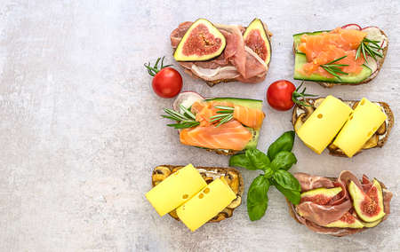 The assortment of homemade toast sandwich with salmon, ham, and cheese on wooden board. Healthy snacks concept, copy space. 版權商用圖片