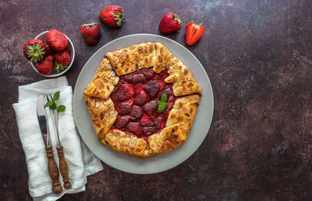 Galette with strawberries. Vegetarian healthy berry tart. Delicious summer food dessert. Copy space for recipe or text.
