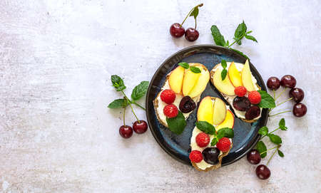 Delicious french toast with fresh fruits, berries, and honey. Tasty breakfast scene or dessert with bread, raspberries, cherries, peach, and ricotta. Copy space, view over above.