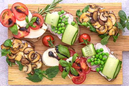 Healthy vegetarian toast assortment with mushrooms, tomatoes, green peas, and cucumber. Flat lay over a wooden board. 版權商用圖片